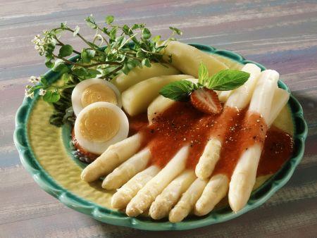 Erdbeersoße auf weißem Spargel dazu Ei und Salzkartoffeln