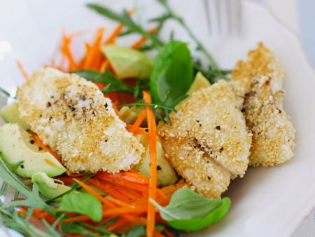 Fisch mit Sesamkruste auf einem Möhren-Avocado-Salat auf einem Teller angerichte