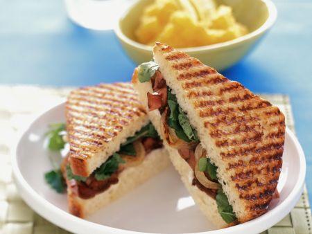 Gegrilltes Sandwich mit Roastbeef, Salat und Zwiebeln