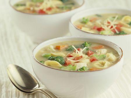 Drei weiße Schälchen gefüllt mit bunter Gemüsesuppe und Tortellini