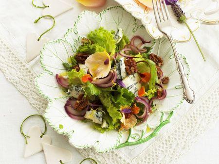 Grüner Salat mit Blauschimmelkäse, essbaren Blüten und Pecanüssen