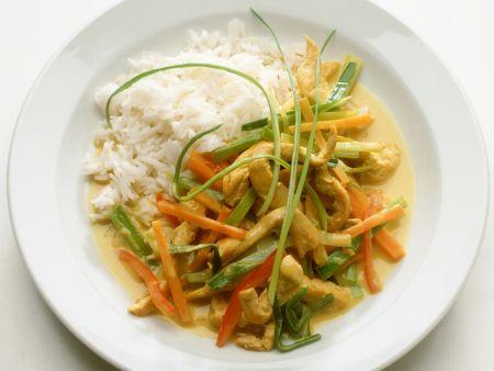 Hähnchenstreifen mit Gemüse und Kokossoße aus dem Wok, dazu Reis