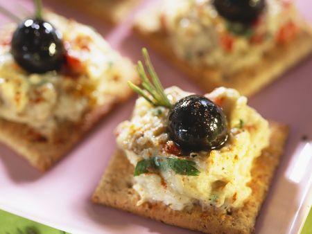 Häppchen mit Auberginenaufstrich und schwarzen Oliven