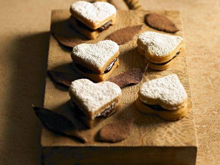 5 Herz-Kekse mit Schkoladenfüllung und Puderzucker bestäubt auf einem Holzbrett