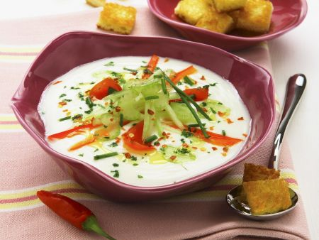Helle Suppe in violetter Schale mit Gemüse-Topping und Toast