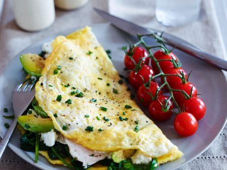 Omelett mit Spinat-Avocadofüllung und Tomaten auf einem Teller