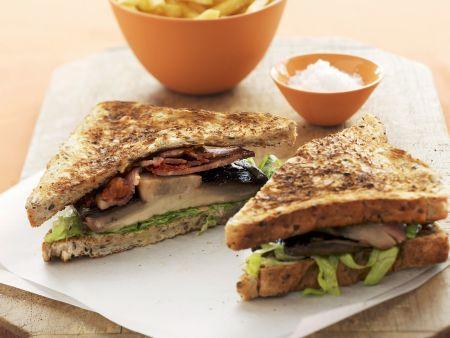 Sandwich mit Speck, Tomate, Salat und Champignons
