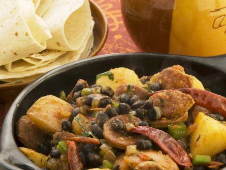 Scharfe spanische Wurst (Chorizo) mit schwarzen Bohnen und Kartoffeln