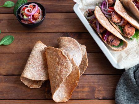 Drei Taco Shells ungefüllt auf einem Brett, daneben gefüllt Tacos