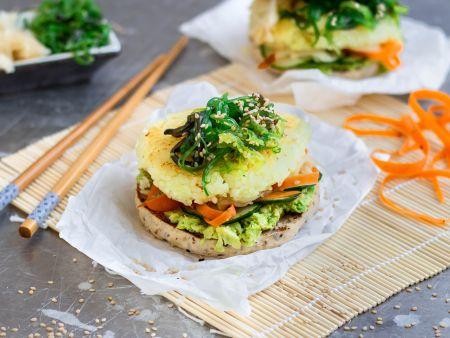 Burger mit Reisbratling und Algensalat auf einer Bambusmatte