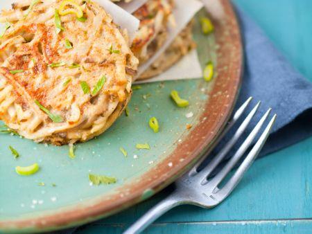 Topinambur-Pufferauf einem Teller mit Frühlingszwiebeln und Salz überstreut