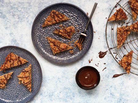 Vegane Nussecken mit Zartbitterschokolade, angerichtet auf blauem Teller und Kuchengitter