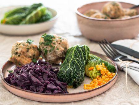 Vegane Wirsingrouladen mit Rotkohl und Semmelknödeln auf einem rosa Teller