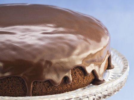 Veganer Schokoladenkuchen mit Schokoglasur auf einer Kuchenplatte