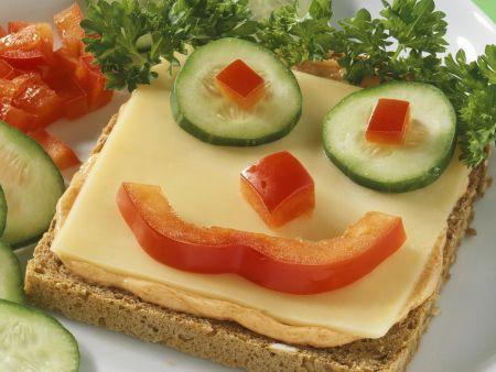Witziger Toast mit Käse und Gemüsegesicht