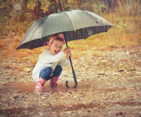 Fröhliches Kind trotzt dem Herbstwetter mit einem großen Schirm