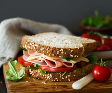 Belegtes Sandwich mit Käse, Schinken, Tomaten und Salat
