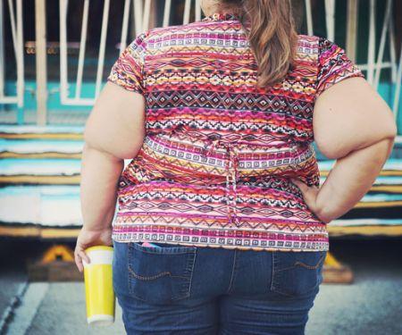 Rückansicht einer fettleibigen Frau mit Softdrink in der Hand