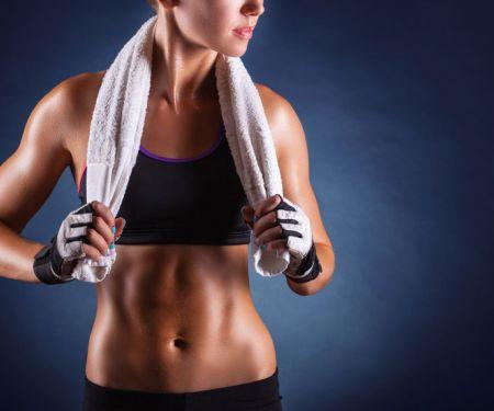 Schlanke Frau in Bustier mit definierten Bauchmuskeln und Handtuch im Nacken