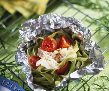 Grüne Nudeln mit Fisch und Tomaten