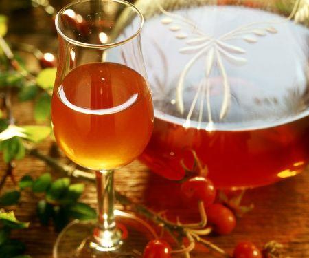 Hagebuttenlikör in Glas und Flasche