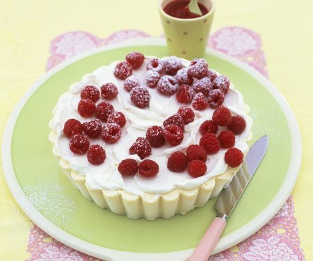 Kuchen mit weißer Schokoeiscreme und Himbeeren