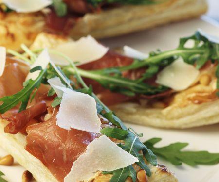 Pizzaschitten mit rohem Schinken, Rauke und Parmesan