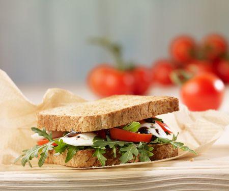 Sandwich aus Vollkorntoast mit Mozzarella, Tomate und Rucola