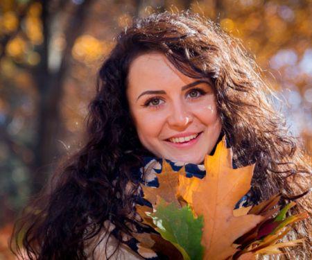 Attraktive Frau mit dickem Schal hält ein herbstliches Blatt vor dem Körper
