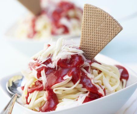 Spaghetti-Eis mit Erdbeersoße und weißen Schokoraspeln
