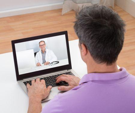 Mann chattet per Video-Konferenz mit seinem Arzt