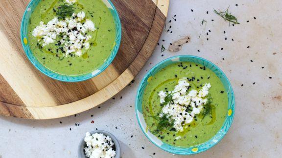 Grüne Suppe in zwei Schalen mit weißem Topping