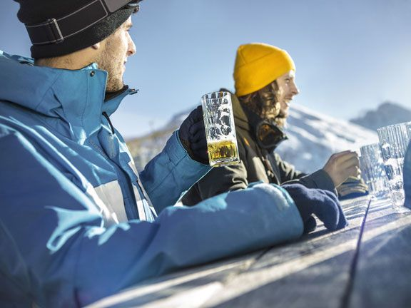 Zwei Skifahrer trinken auf der Alm Weizenbier