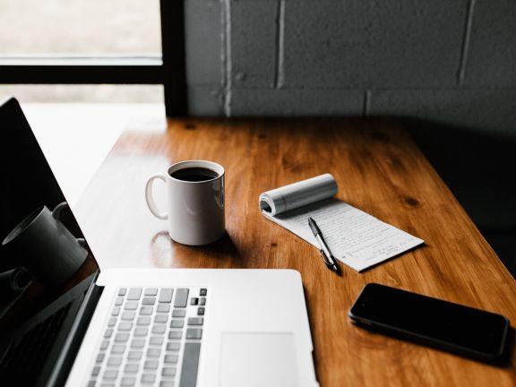 Macbook und To-Do-Liste mit Kaffeebecher und Stift auf einem Tisch