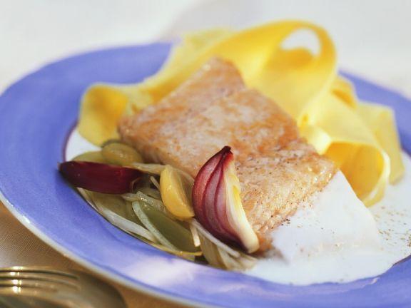 Bandnudeln mit Lachsfilet und Riesling-Trauben-Sauce und roten Zwiebeln