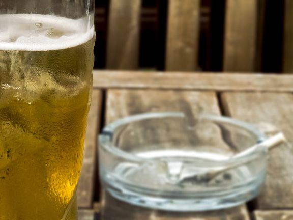 Ein Glas Bier und eine brennende Zigarette in einem Aschenbecher auf einem Tisch