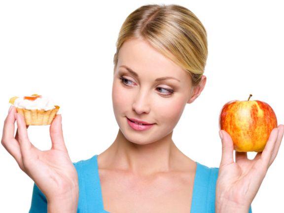 Frau hat die Wahl zwischen Apfel und Muffin