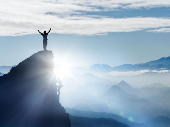 Mensch steht auf einem Berggipfel und reckt die Arme nach oben
