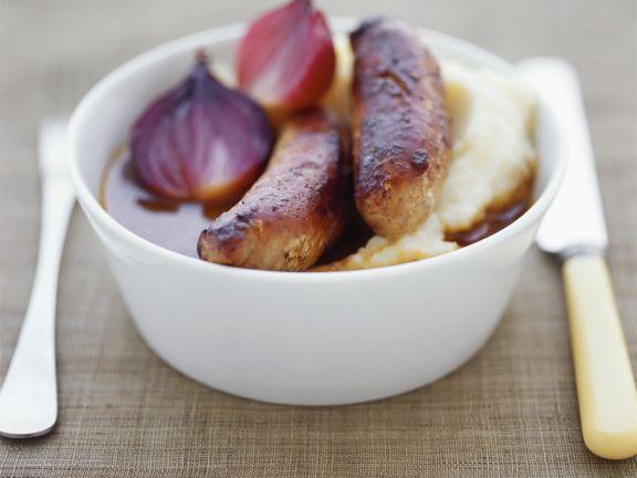 Bratwürsten mit Kartoffelbrei und Zwiebelsoße