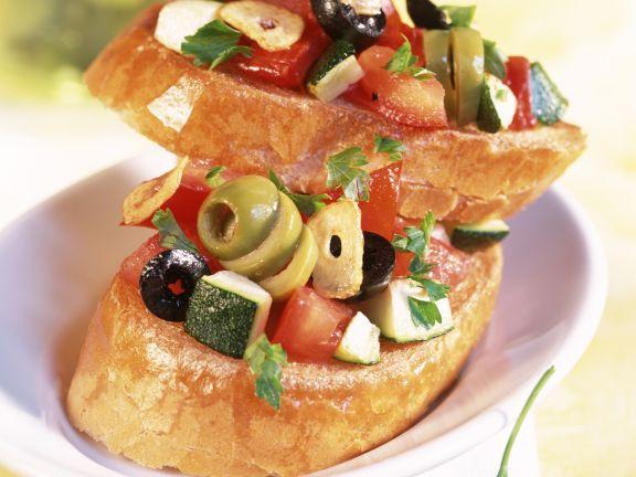 Bruschetta mit Oliven, Tomaten und Zucchini