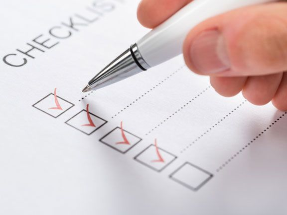 Hand mit Kugelschreiber beim Ausfüllen einer Checkliste