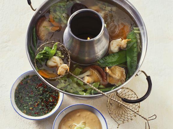 Chinesischer Feuertopf mit Rinderfilet, Gemüse und zwei Dips