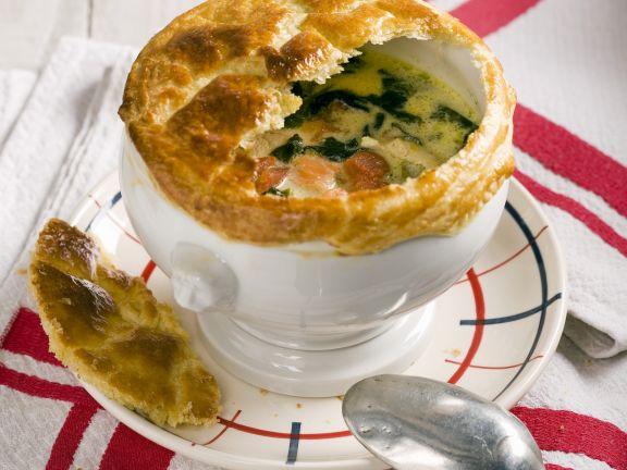 Deftige Suppe mit Hühnchen, Lachs, Spinat und Blätterteighaube