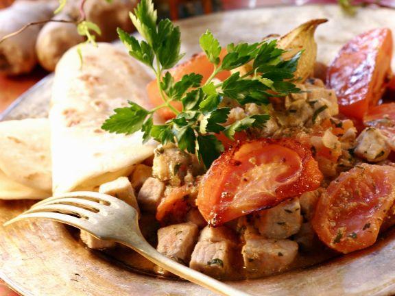 Deftiges Schweinefleisch mit Tomaten dazu indisches Fladenbrot (Chapati)