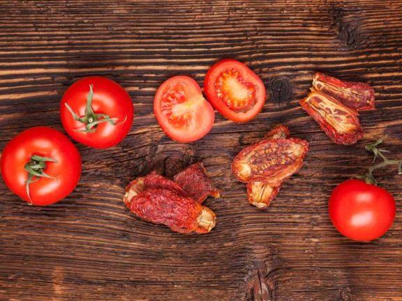 Getrocknete und frische Tomaten auf einem hübschen Holzbrett