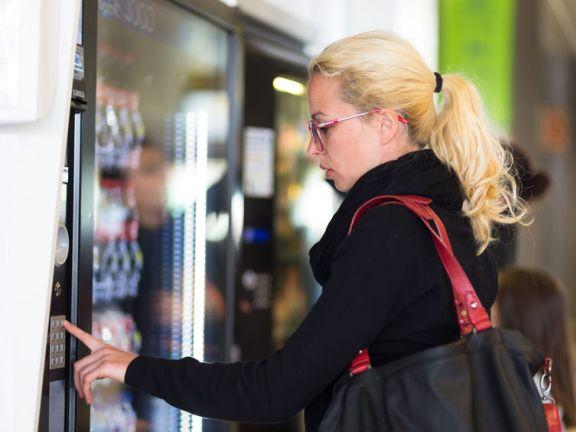 Frau trifft eine Auswahl an einem Snackautomaten