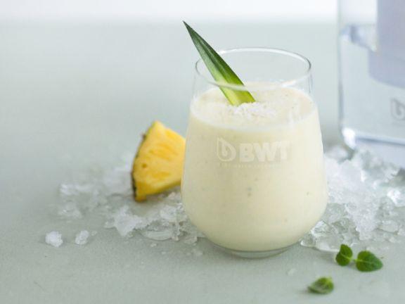 Exotischer Smoothie mit Ananas und Kokosflocken