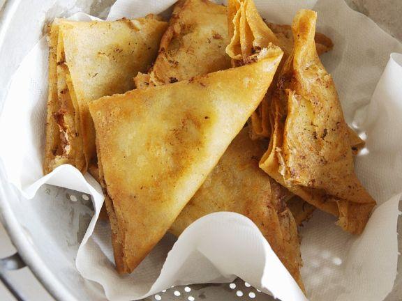 Filoteigtaschen mit Kartoffelfüllung abtropfen lassen