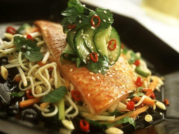 Fischfilet auf gebratenen Nudeln mit Gemüse