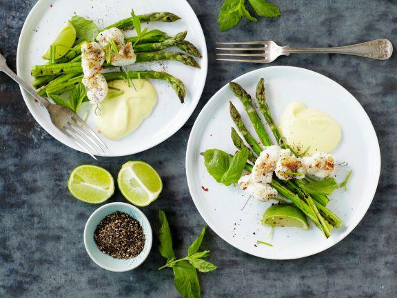 Fischspieße auf grünem Spargel mit Limettensauce